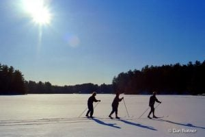 3 skiers on lake